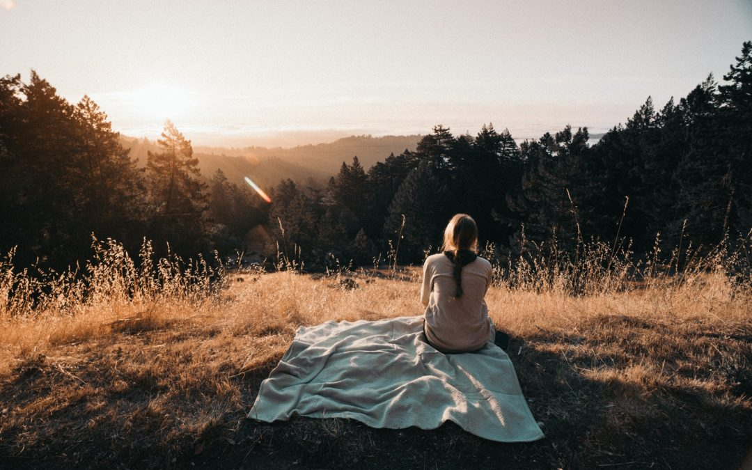 Young woman with brain sitting on a blanket looking over distant hills
