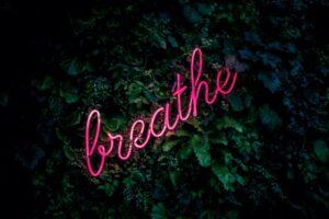 In neon pink script, the word breathe